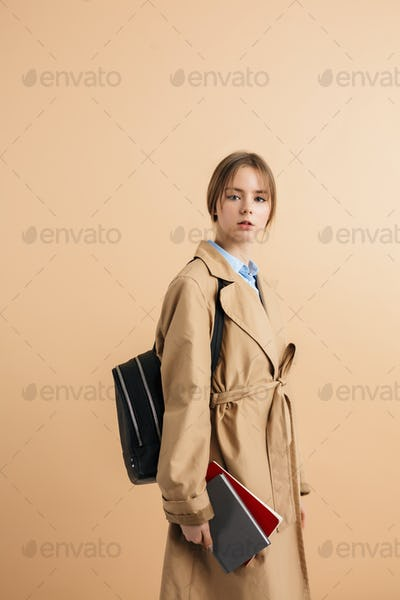 Young beautiful school girl in trench coat thoughtfully looking in camera