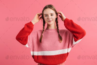 Young pretty smiling girl with braids in sweater straightening her hair happily looking in camera