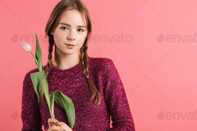 Young smiling girl with braids in sweater holding tulip flower in hand dreamily looking in camera