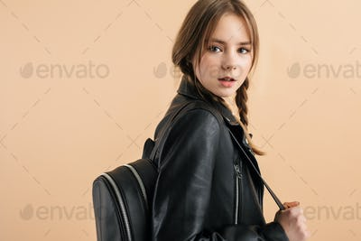 Young school girl with braids in leather jacket dreamily looking in camera