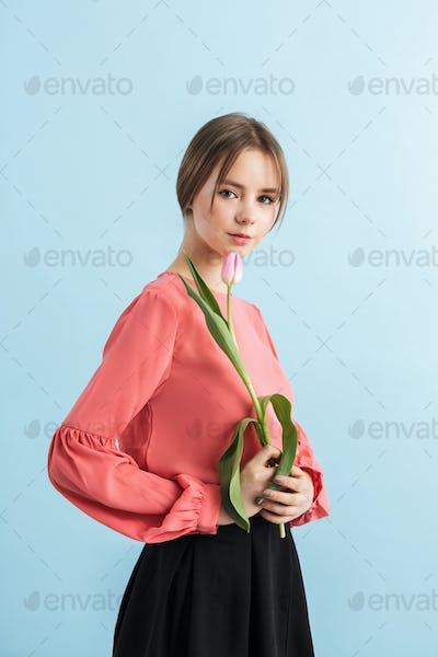 Young pretty girl in blouse holding pink tulip flower in hand thoughtfully looking in camera