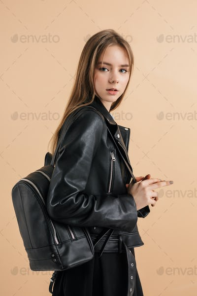 Young beautiful schoolgirl in leather jacket with backpack thoughtfully looking in camera