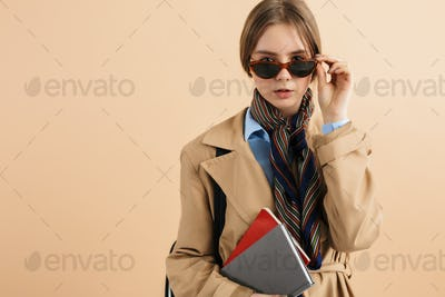 Young stylish dreamy girl in trench coat and sunglasses with notepad curious looking in camera