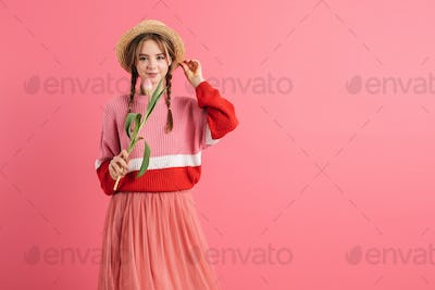 Young smiling girl with two braids in sweater and straw hat holding one tulip in hand happily