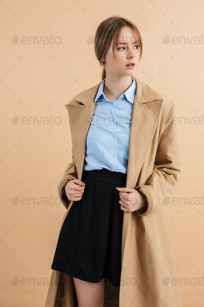 Young beautiful lady in trench coat and blue shirt dreamily looking aside over beige background