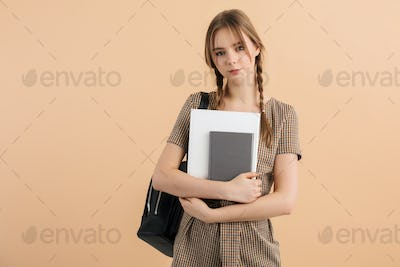 Young pretty smiling school girl with braids in tweed jumpsuit with backpack holding notepads
