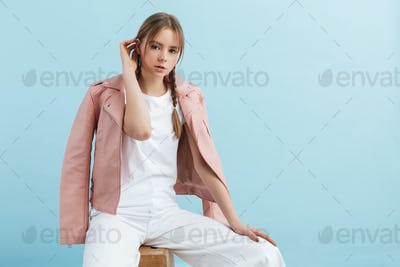 Young beautiful girl with braids in pink leather jacket and white jeans dreamily looking in camera