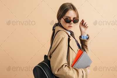 Young beautiful girl in trench coat and sunglasses with backpack on shoulder holding notepads