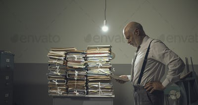 Businessman checking files and piles of paperwork