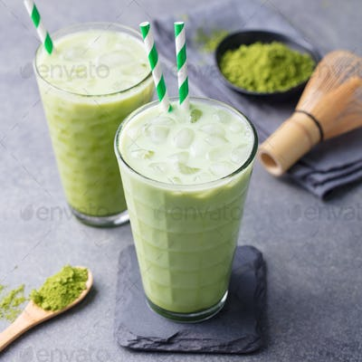 Matcha Green Tea Ice Latte with Matcha Powder and Bamboo Whisk. Grey Background. Close up.
