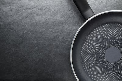 Black skillet with non-stick surface on slate background