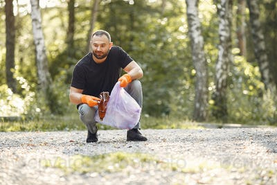 Man collects garbage in garbage bags in park