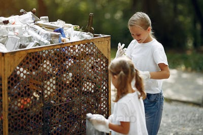 Children collects garbage in garbage bags in park