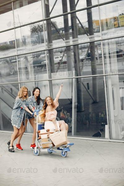 Three beautiful girls standing by the airport