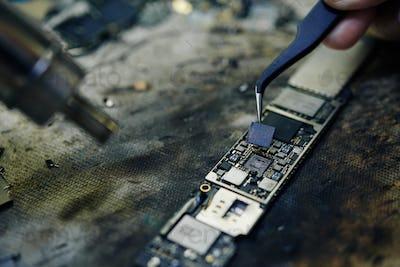 Repairman taking small parts of logic board