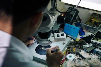 Repairman with microscope checking logic board