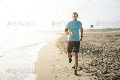 Handsome man running on the beach