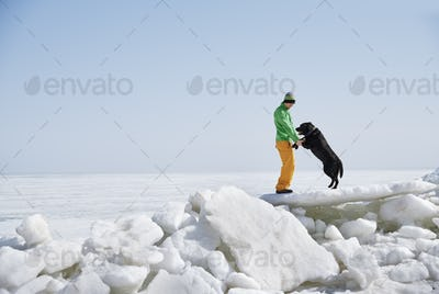 Young adult man outdoors with his dog having fun in winter landscape