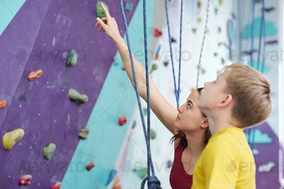 Young instructor showing schoolboy some dangerous places on climbing wall