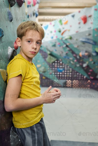 Cute schoolboy in activewear leaning against climbing wall or equipment