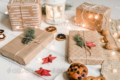 Packed gifts among decorative red stars, walnuts, sparkling garlands on table
