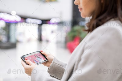 Contemporary young woman with smartphone surfing in online shop