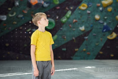 Contemporary active schoolboy in yellow t-shirt and grey pants