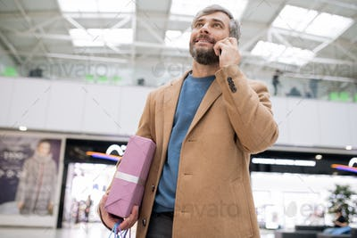 Happy bearded man in coat holding giftbox and talking to someone on smartphone