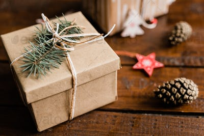 Wrapped and packed giftbox with conifer on top on wooden table