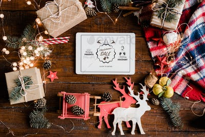 Christmas sale announcement on display of touchpad surrounded by decorations