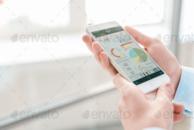 Young economist or financial analyst holding smartphone with charts and diagrams