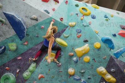 Young sportswoman holding by one of artificial stones on climbing wall