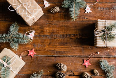Christmas background made up of giftboxes, pinecones, conifer and decorations