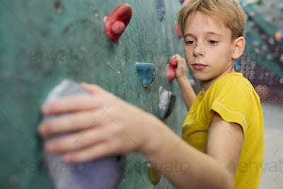 Young schoolboy in yellow t-shirt holding by small rocks on climbing wall