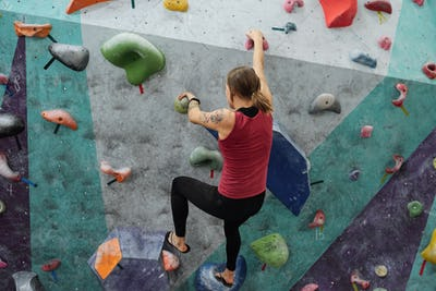 Rear view of young sportswoman grabbing by small rocks on climbing wall