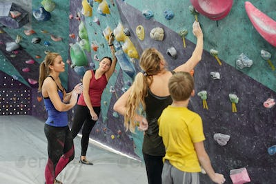 Group of active women and youthful boy having break after climbing practice