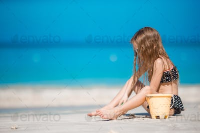 Adorable little girl in swimsuit at tropical beach