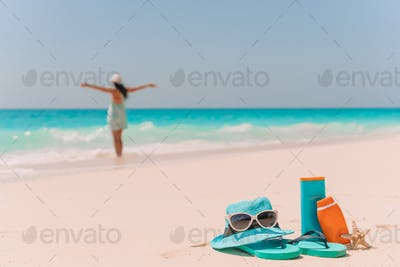 Suncream bottles, sunglasses, flip flop on white sand background ocean