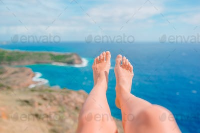 Female feet on white sandy beach in famous place