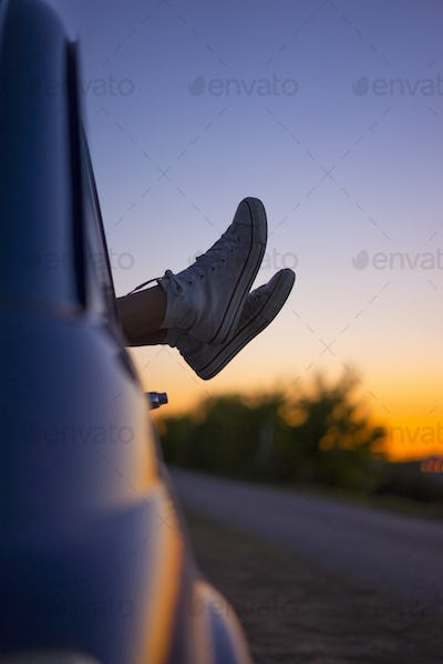 young woman feet out of vintage car window