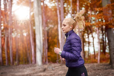 Pensive woman jogging with white earphones