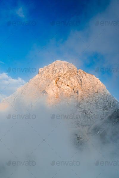 Sunset Illuminated Mangart Mountain Peak Above Clouds, Slovenia