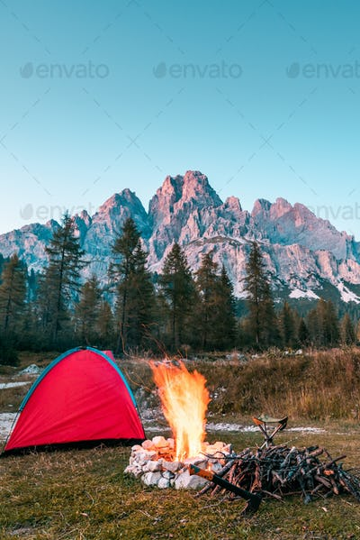 Campfire and Tent in Mountains. Leisure Activity Outdoors