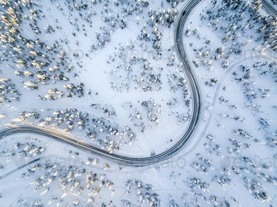 Aerial view of a winter winding road in the snow covered forest in Finland