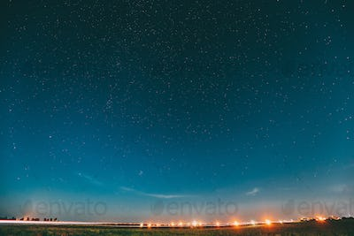 Night Starry Sky With Glowing Stars Above Landscape With City Li