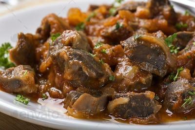 chicken gizzard stew on plate with herbs