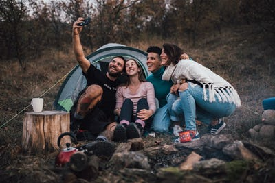 Young friends laughing, taking selfie,hanging out at campsite