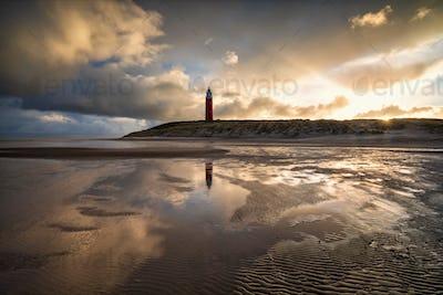 dramatic sunrise behind lighthouse on north sea coast