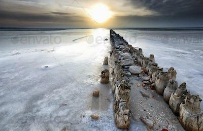 old wooden breakwater frozen on coast