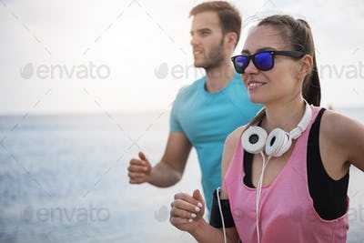 Man and woman jogging together on sunny day